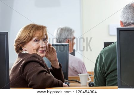 Portrait Of Confident Senior Woman Sitting In Computer Class