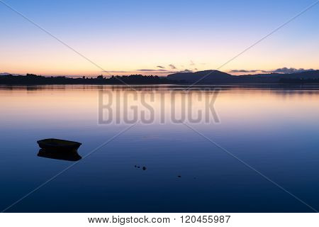 Small Boat Afloat On Calm Bay During Brilliant Sunrise.