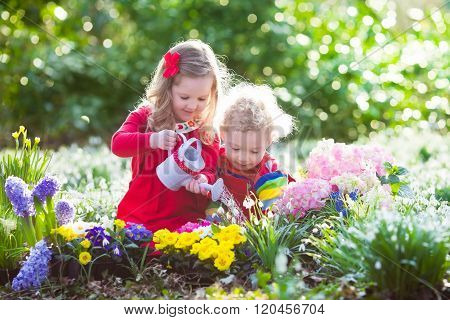 Kids Planting Flowers In Blooming Garden