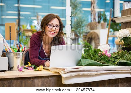 Florist Using Laptop At Counter In Flower Shop