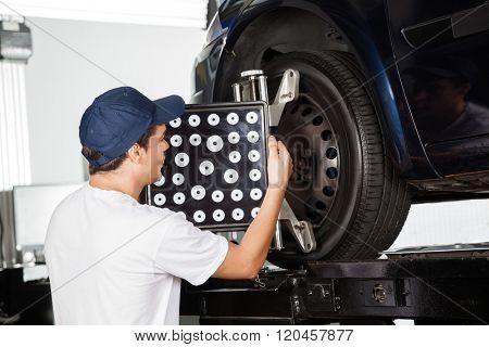 Male Mechanic Adjusting Wheel Alignment Machine