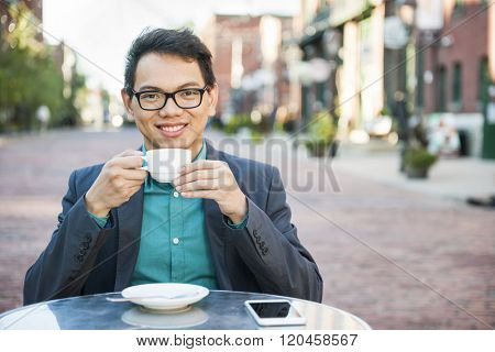 Successful young asian man sitting and smiling in relaxing outdoor cafe with mobile phone holding cup of coffee enjoying his break
