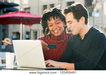 Young couple shopping online together with laptop and credit card buying online with ecommerce. Woman holding credit card and smiling. Portrait couple paying bills online with laptop and credit card.
