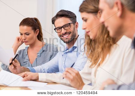 Happy young handsome businessman in a meeting wearing eyeglasses. Successful businessman writing important information in conference. Portrait of business man smiling during a business meeting.