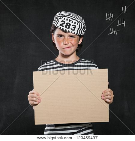 Closeup mugshot photo of boy holding blank sign. Young boy make a face wearing jail suit isolated on black background. Little prisoner showing a cardboard.