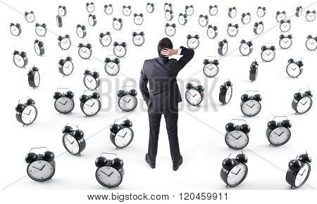 Businessman Surrounded By Alarm Clocks