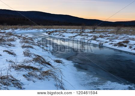 Frozen Stream and Snow Covered Field at Sunset