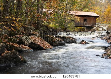 Covered Bridge Over Rushing Water In Autumn