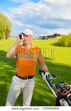 man golfer watching into rangefinder