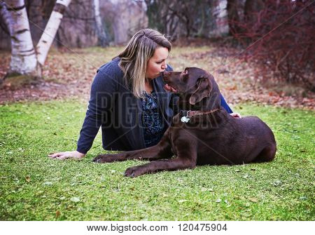 a woman sitting with a dog, a chocolate lab in a park kissing his nose toned with a retro vintage filter instagram app or action effect