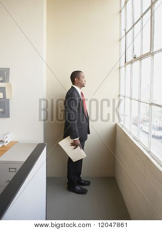 Businessman at window holding documents