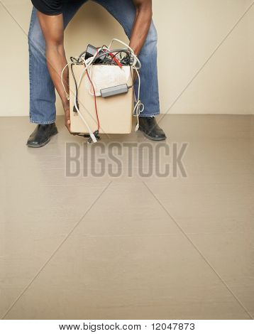 Man lifting cardboard box full of tangled cords