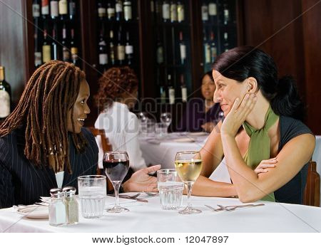 Two women talking at table in restaurant