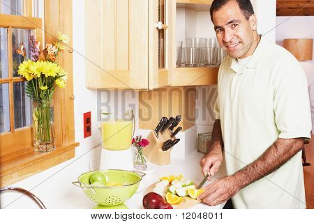 Man chopping fruit in the kitchen
