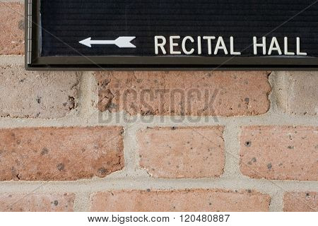 Recital hall sign on brick wall