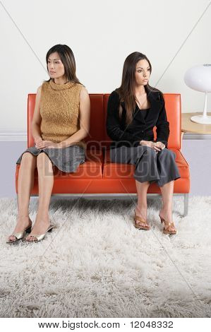 Young women ignoring each other on couch