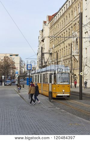 BUDAPEST, HUNGARY - FEBRUARY 02: Pedestrians walking on pavement next to tram line number two near Hungarian Parliament building. February 02, 2016 in Budapest.