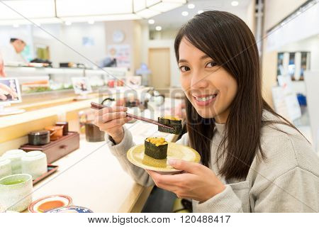 Woman having Conveyor belt sushi in restaurant