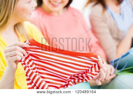 clothing, fashion, style and people concept - close up of happy young women or teenage girls with t-shirt