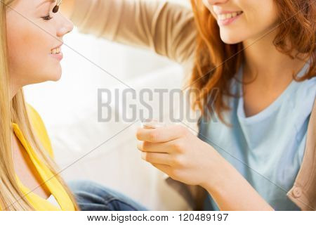 beauty, make up, cosmetics and people concept - close up of smiling young woman and visagist or friend with makeup brush and eyeshadow