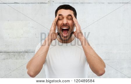 emotions, stress, madness and people concept - crazy shouting man in t-shirt over gray wall background