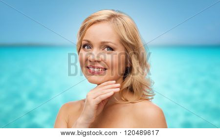 beauty, people and skincare concept - smiling middle aged woman with bare shoulders touching face over blue sea and sky background