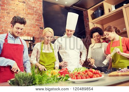 cooking class, culinary, food and people concept - happy group of friends with male chef cook cooking in kitchen