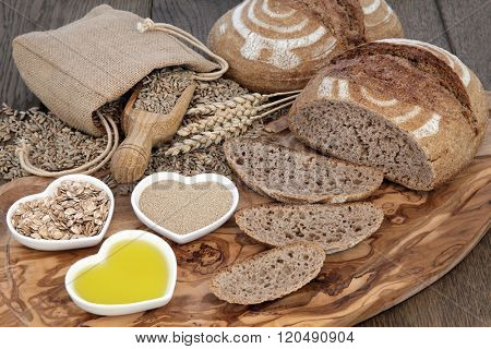 Rustic still life of homemade brown bread sliced loaf, baking ingredients of yeast, oil, rye flakes and wheat in a hessian sack on olive wood board over oak background.