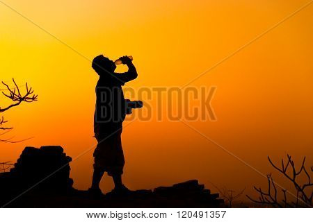 Photographer drinking water after climbing hill , Silhouette people.