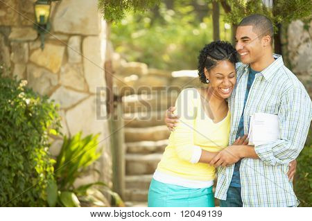 Couple hugging and laughing outdoors