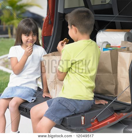 Brother and sister eating cookies in back of van