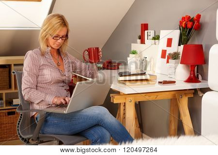 Young woman browsing internet on laptop computer, sitting at home in study.