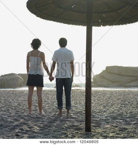 Young couple holding hands underneath umbrella on beach