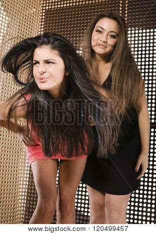 two pretty girlfriends at party dancing smiling close up, fancy fashion dresses creative interior ba