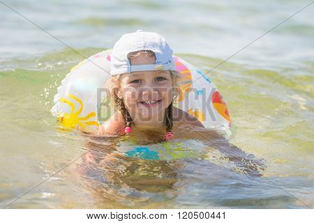 Four-year Girl Floats With A Circle In The Sea Water