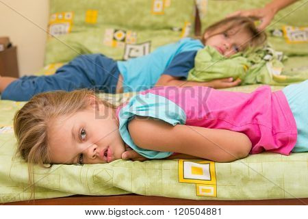 Two Girls Lie On A Bed On The Opposite Sides