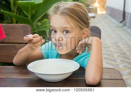 Six-year Girl With Pleasure Eats Porridge For Breakfast