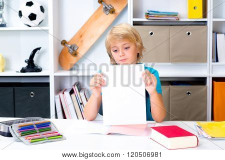 Boy On Desk With Bad Report Card