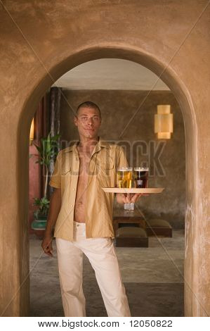 Portrait of man holding tray of drinks