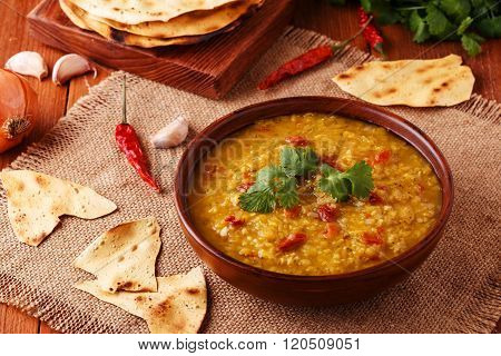 Thick indian red lentil soup with cilantro served with indian flat bread on a wooden background.
