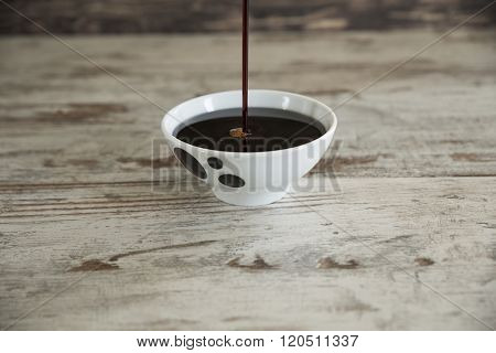 Grape molasses flowing to bowl on wooden background.