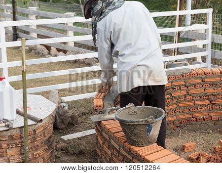 LAMPANG, THAILAND - MARCH 1, 2016: The mason worker is laying the brick in Wang Nua Sweety which is the travelling attraction in Lampang Thailand on March 1 2016.