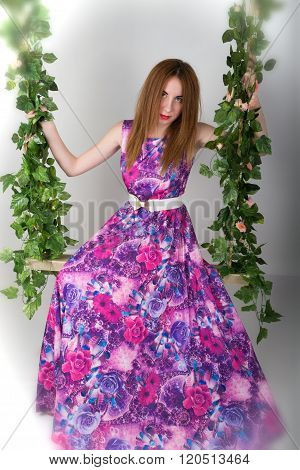 Beautiful young leggy redhaired woman in a long colorful dress on a swing, wooden swing suspended fr