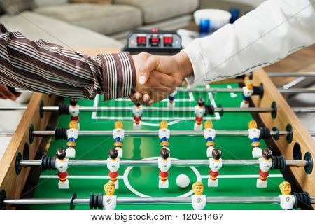 Shaking hands over foosball table