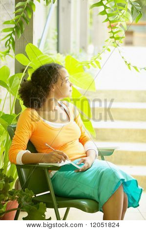Profile of woman writing in date book outdoors