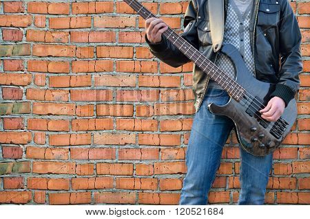 Man Plays Electric Guitar On The Background Brick Wall
