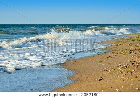 Sea Waves Wash The Beach Against A Blue Sky