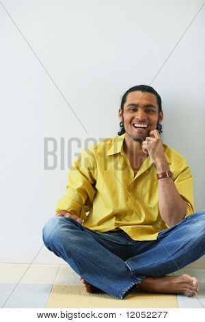 Portrait of man sitting cross legged on floor laughing