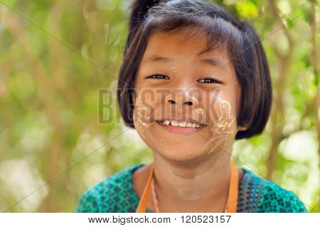 SANGHLABURI, THAILAND, JANUARY 24, 2016 : A Thai little girl with Burmese Thanaka cosmetic powder is posing near a temple in Sanghlaburi, Thailand