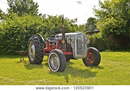 Old Ford tractor parked in the yard